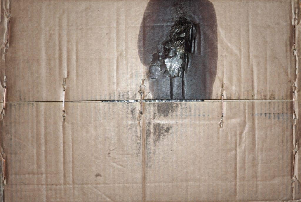 grunge dirty brown corrugated cardboard texture with stains of motor engine lubricant oil useful as a background