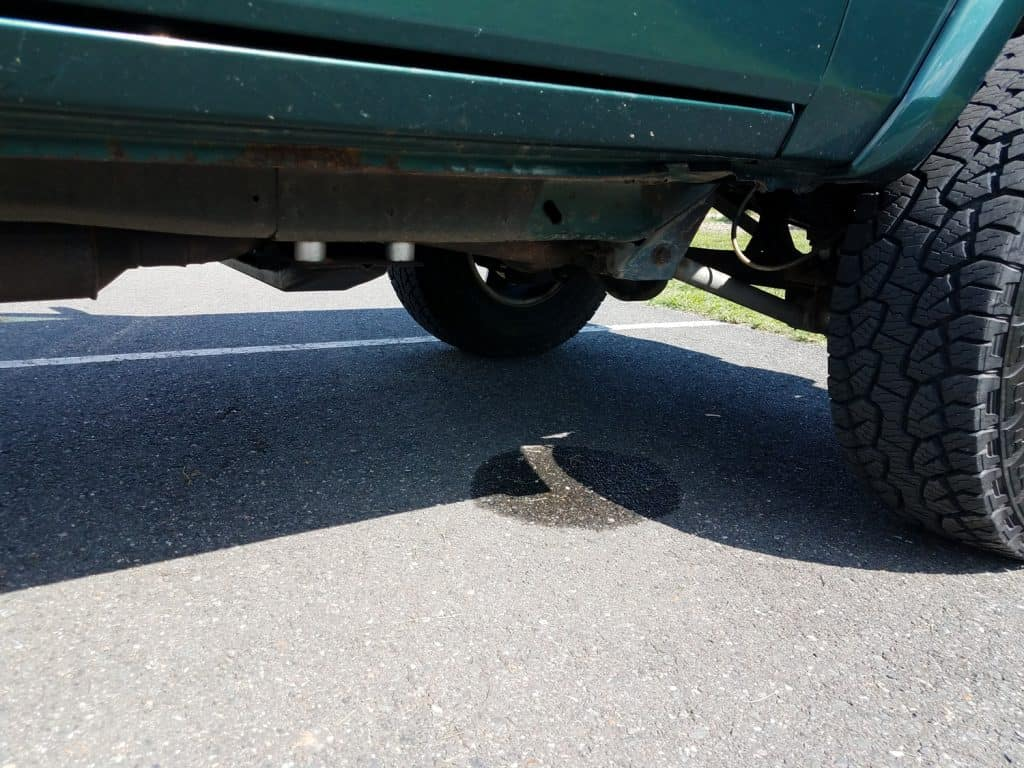 liquid puddle from leak or drip under green car or vehicle