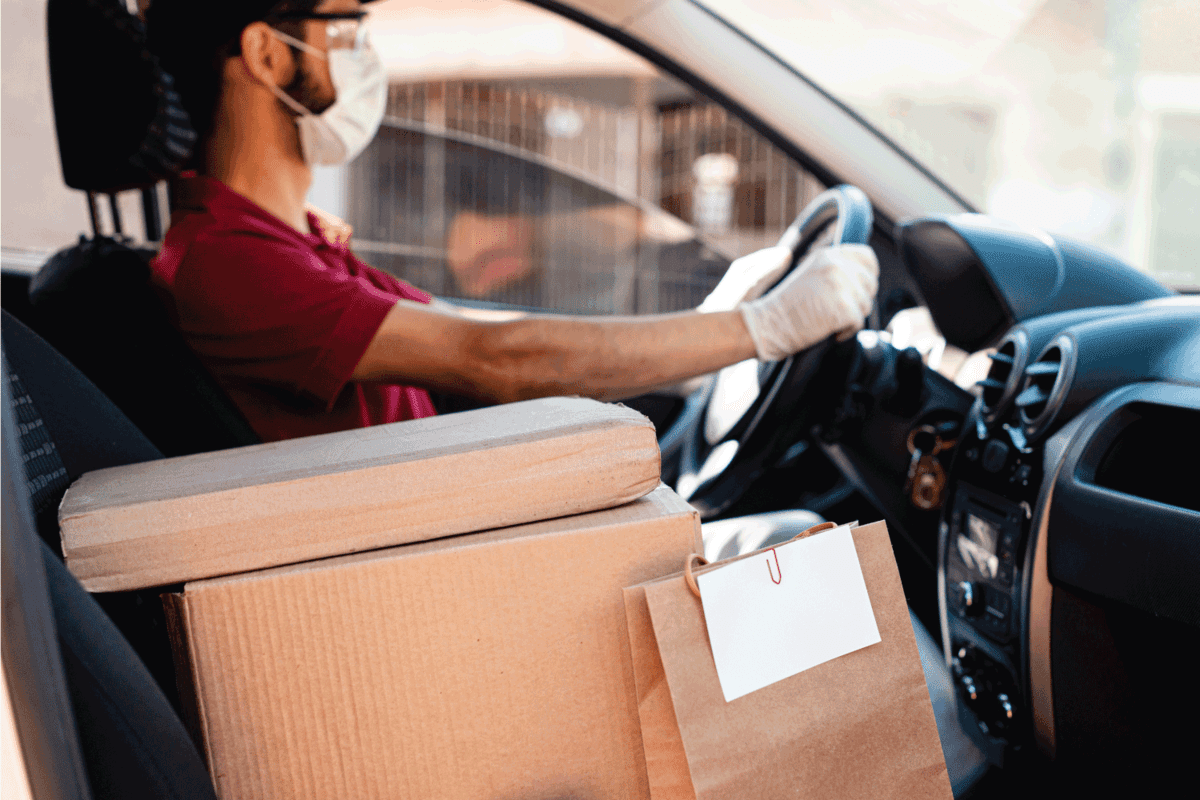 male courier with orders in car. Food delivery service. Can You Have A Passenger While Driving For Uber, Lyft, Uber Eats, Or Doordash