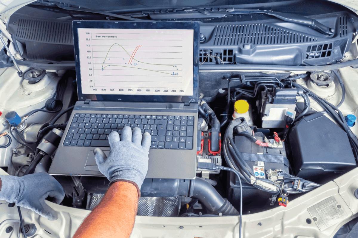 mechanic using laptop in an open engine bay to setup ECU