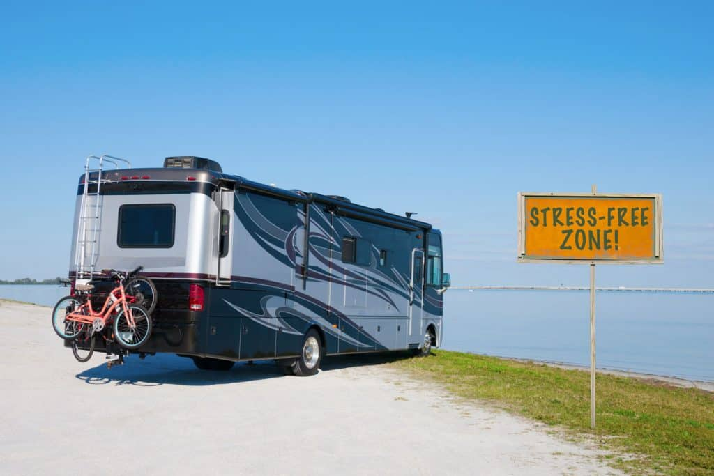 A class A motorhome parked near the coastline fronting a gorgeous panoramic view of the ocean