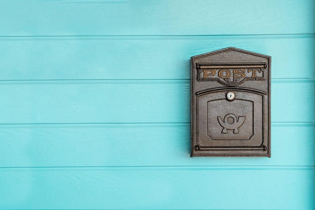 A cyan colored wall with a metal mailbox hanged