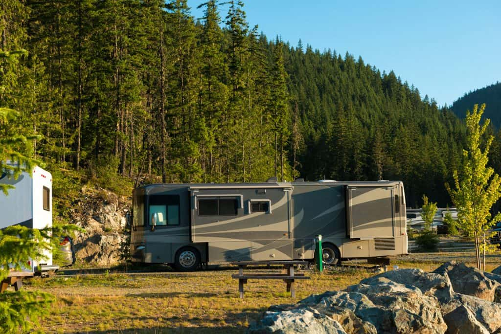 A gorgeous black and gray colored luxurious motorhome park on the parking grounds of a national park