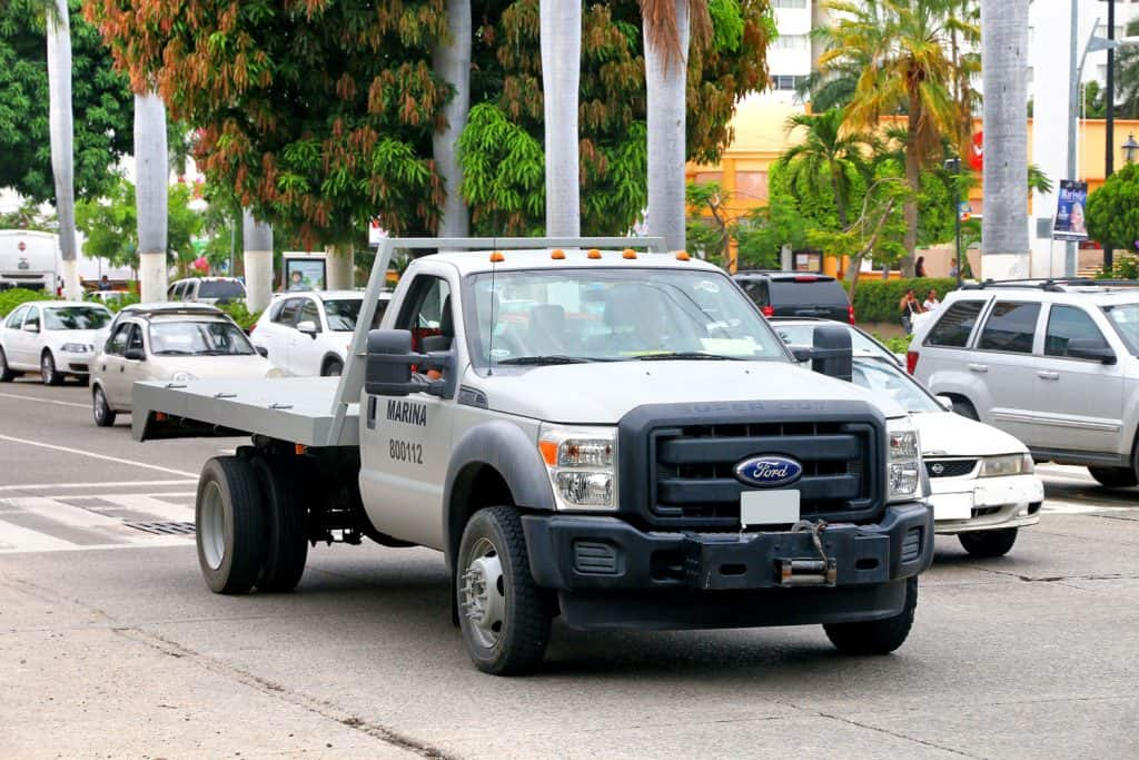 A huge Ford F-550 moving slowly at light moving traffic