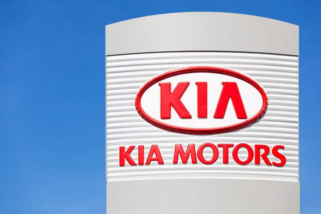 A huge Kia motors logo on the side at a Kia dealership