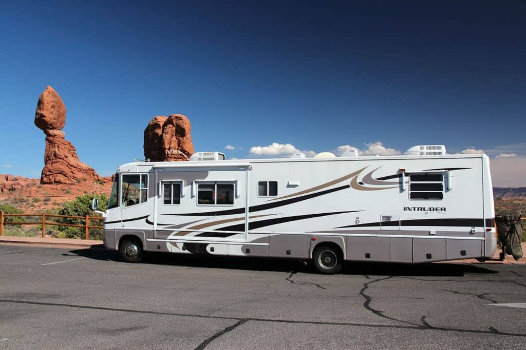A long class A motorhome parked on the side of the road next to a breathtaking view