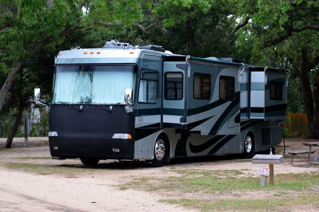 A luxurious class A motorhome parked on the side of a camping ground