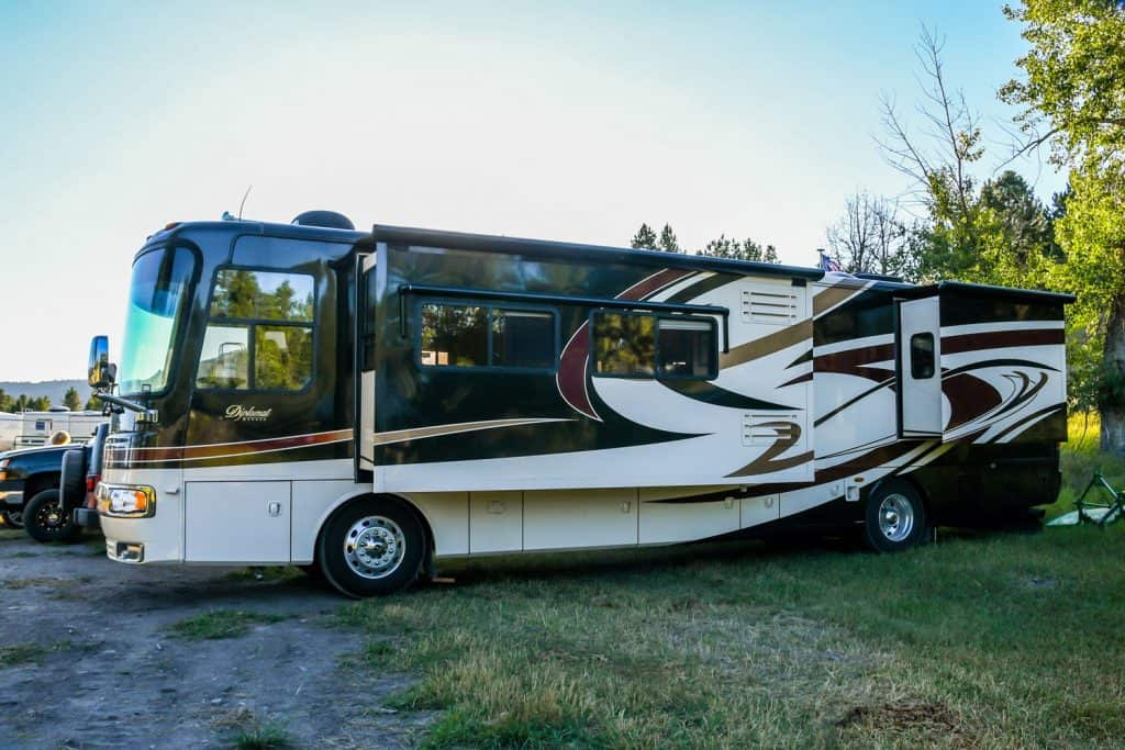 A luxurious long class A motorhome parked on the camping ground