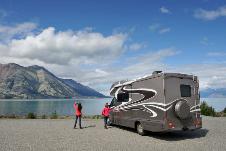A mother and daughter parking their black and white colored RV near the lake, 15 Amazing RV Exterior Paint Ideas