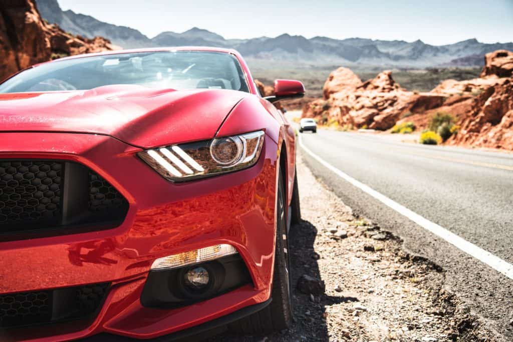 A red colored Ford Mustang GT parked on the side of the road