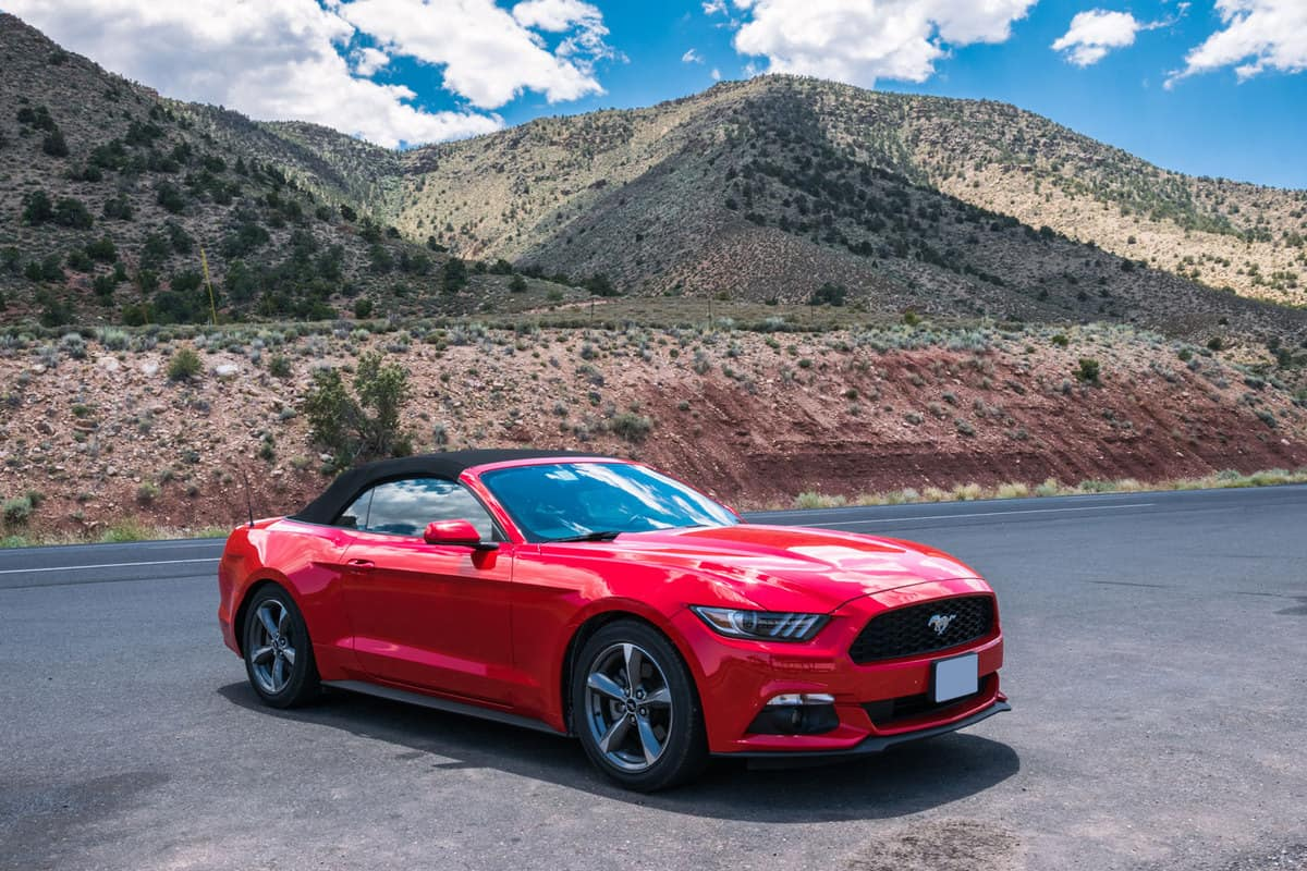 A red colored convertible Ford Mustang GT parked on the middle of the road