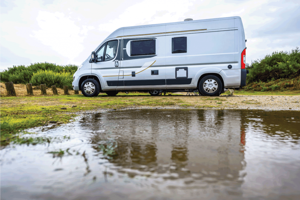 Campervan or motorhome camping on rainy day with rain puddles. How Much Does It Cost To Replace RV Water Heater