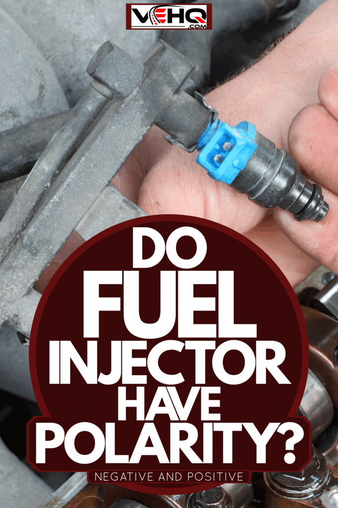 A mechanic holding a fuel injector of an engine, Do Fuel Injectors Have Polarity? [Negative And Positive]