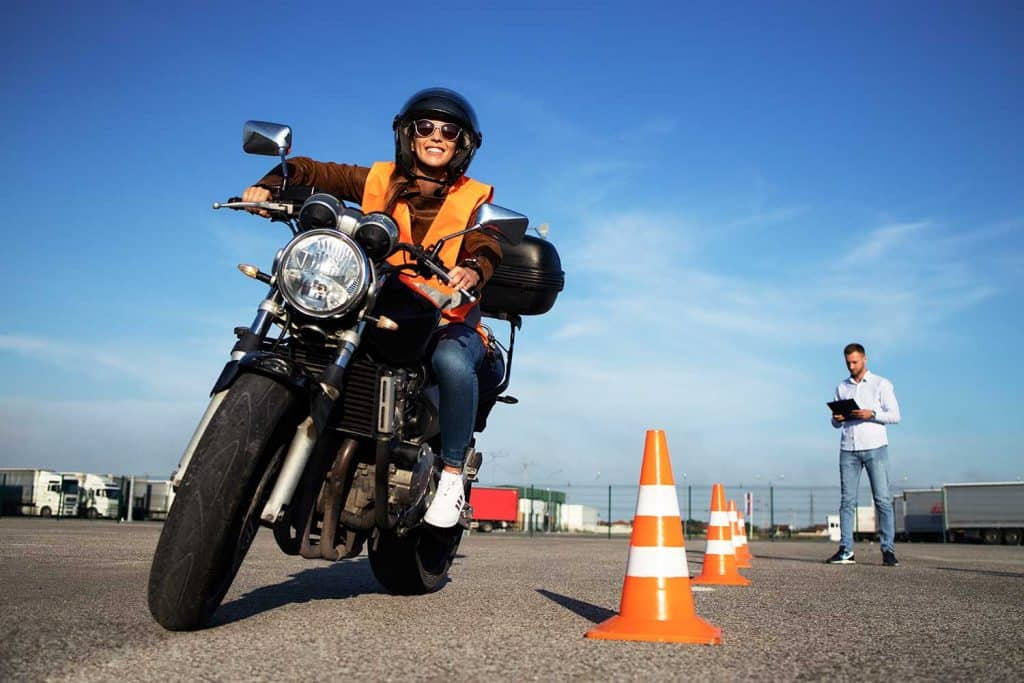 Female student with helmet taking motorcycle lessons and practicing ride
