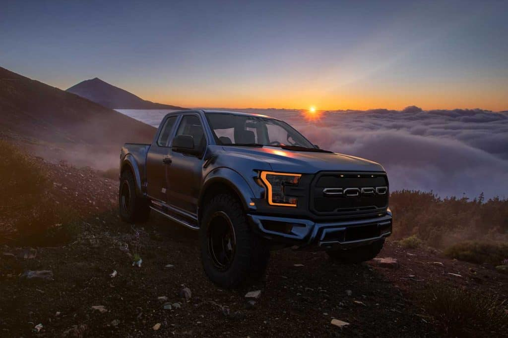 Ford Raptor standing on the slope of the volcano above the cloud