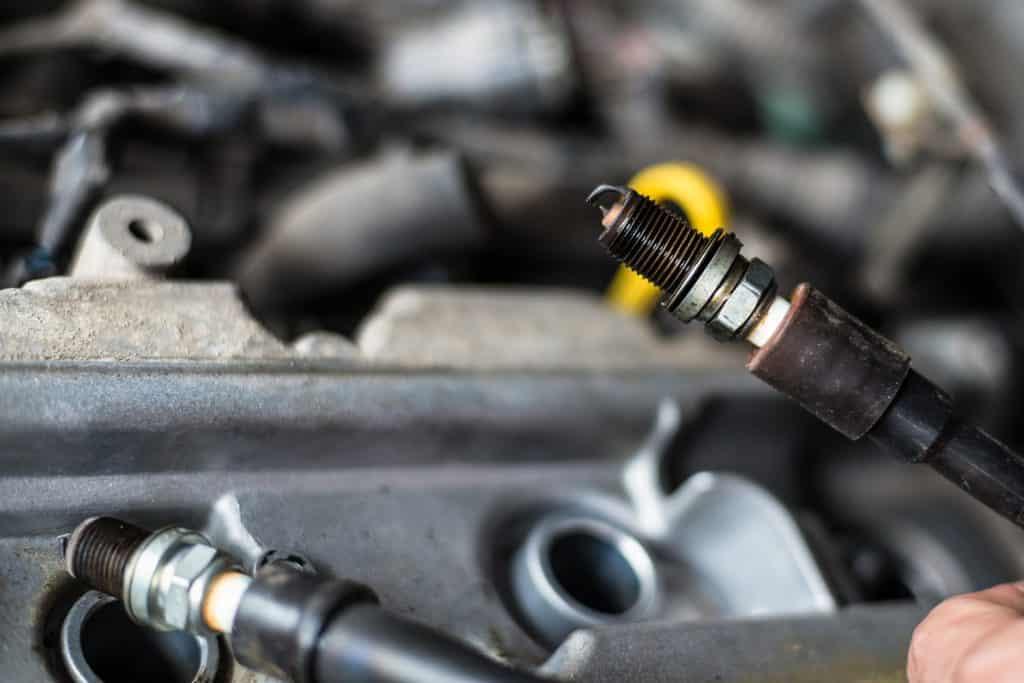 Mechanic changing broken car spark plugs. Car repair. Replacement of spark plugs