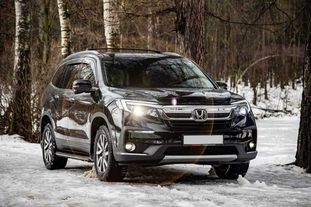 New off-road car Honda Pilot 3 generation black in winter off-road in the forest