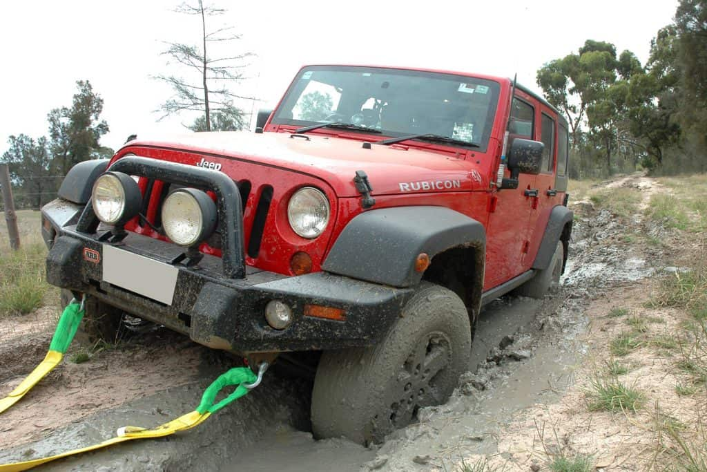 Red 2007 Rubicon Jeep JK Wrangler stuck in mud on the border track between South Australia and Victoria. This Jeep is being recovered by using a snatch / tow strap