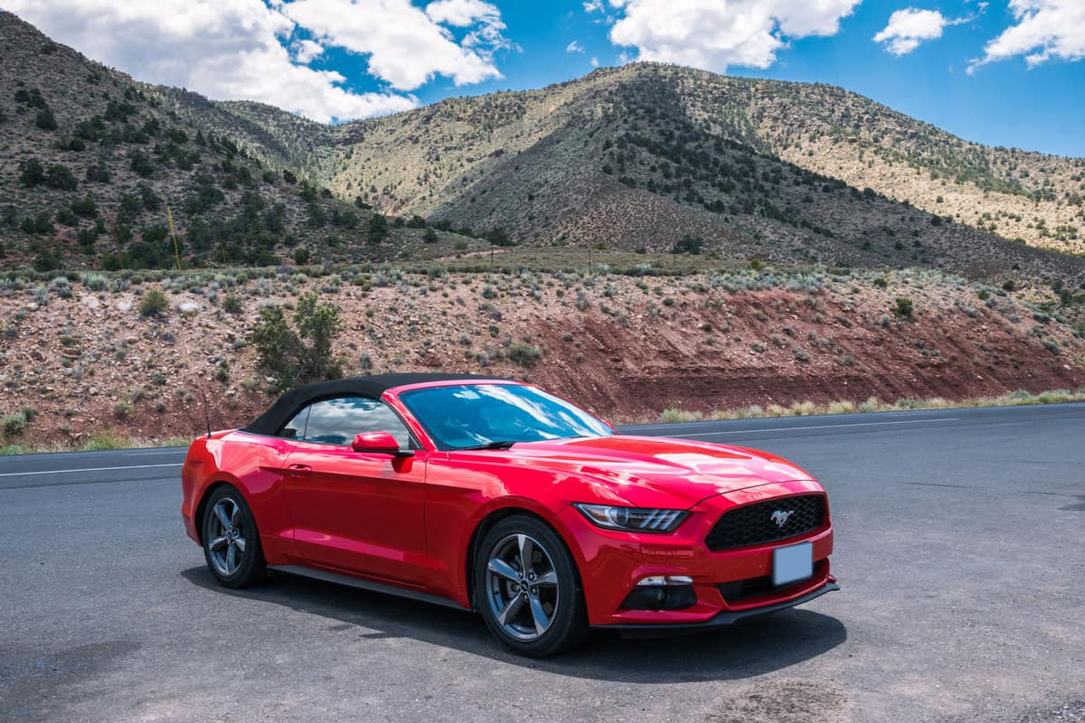Red cabriolet car Ford Mustang in Crand Kenyon Village, Grand Canyon National Park, Arizona, USA., How To Reset A Battery Light On Ford Mustang