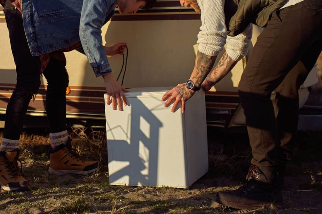 Two young men carrying refrigerator for New Year party in front of their camper trailer, RV Dometic Fridge Not Working - What To Do?