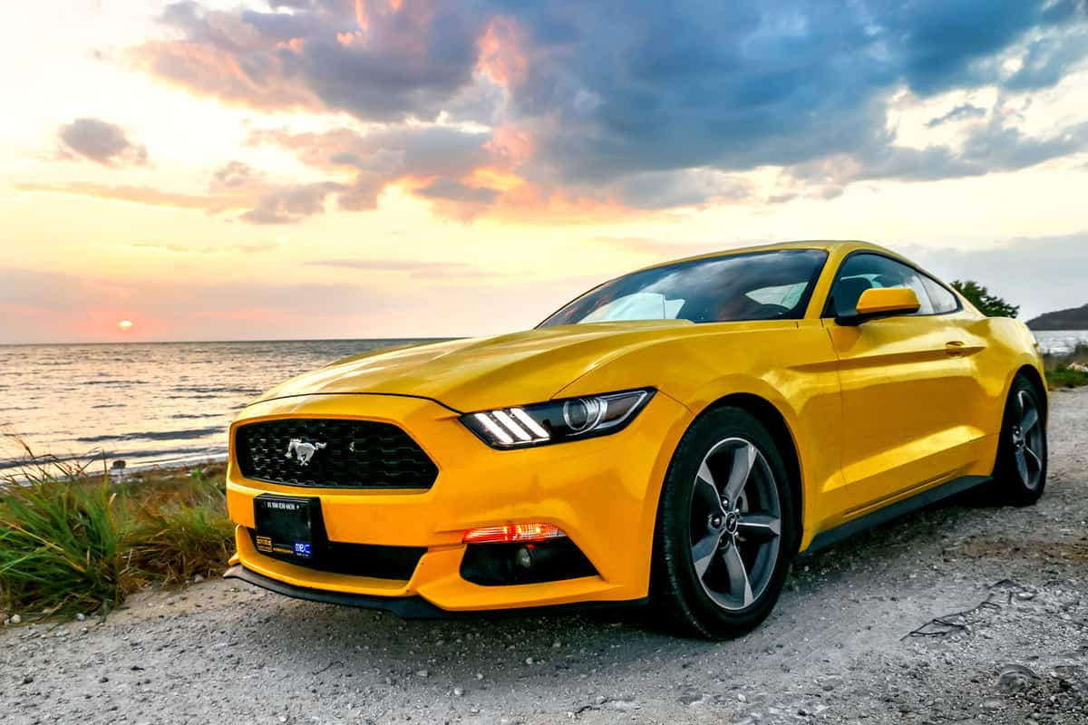 Yellow muscle car Ford Mustang at the countryside.