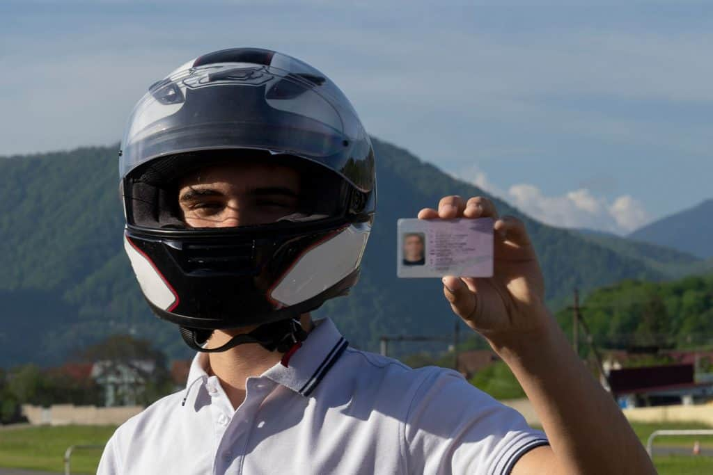 Young man in a helmet on the motorbike is showing driving license, How To Get A Motorcycle License In California?