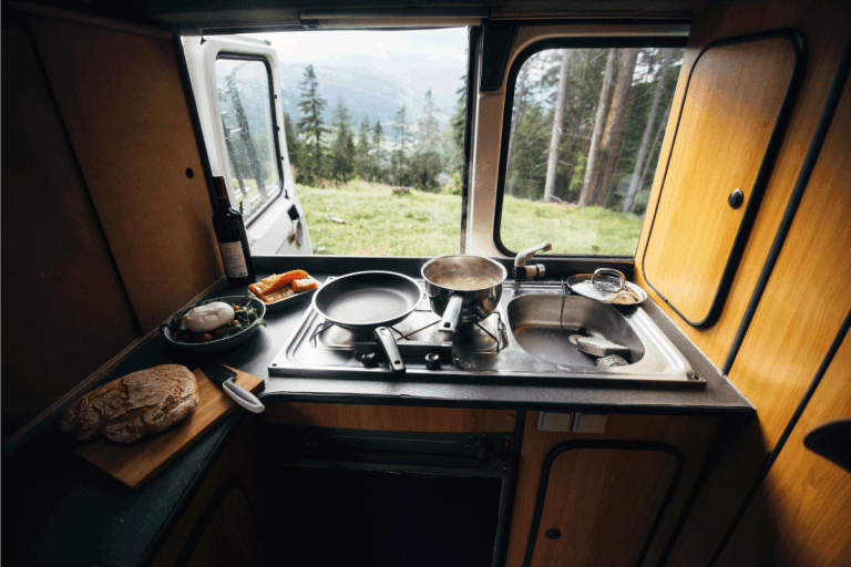 Interior of travel camping van or camper RV with stove and sink. Vanlife lifestyle vibes, cooking on campsite during road trip with amazing view of mountains. 11 Awesome RV Kitchen Ideas