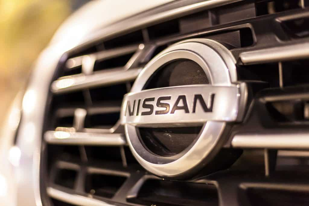A Nissan on the grill of a car