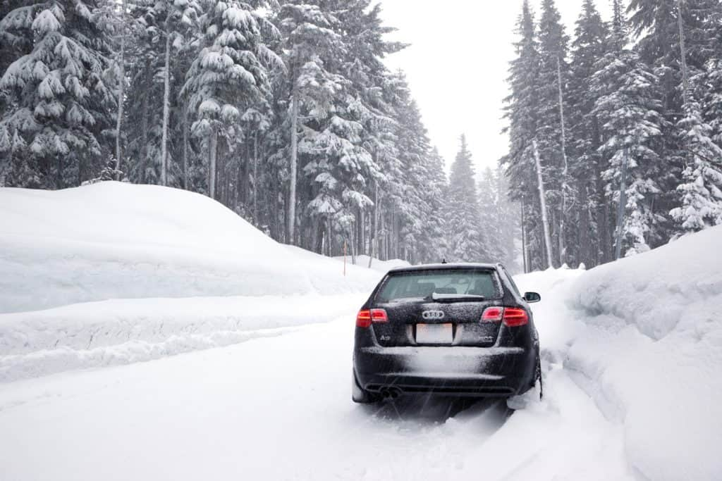 A black 2011 Audi A3 quattro on mountain road with deep snow during a winter storm in the Oregon Cascade Mountains