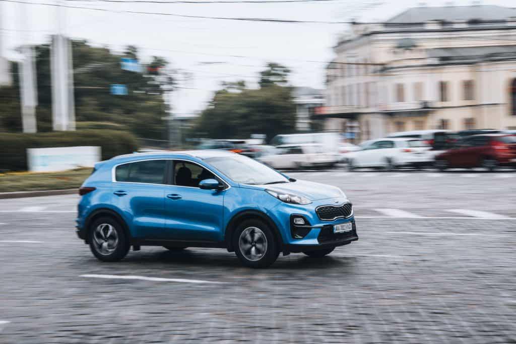 A blue Kia Sportage on the parking lot
