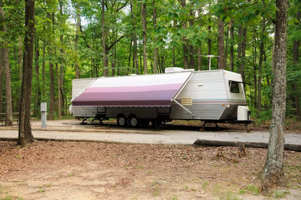 A huge trailer parked on the camping ground with a light purple colored awning