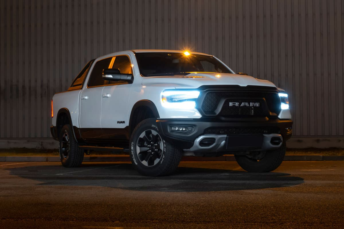 A huge white Ram 1500 parked near a building with its lights turned on, How Much Weight Can A Ram 1500 Hold In Its Bed?