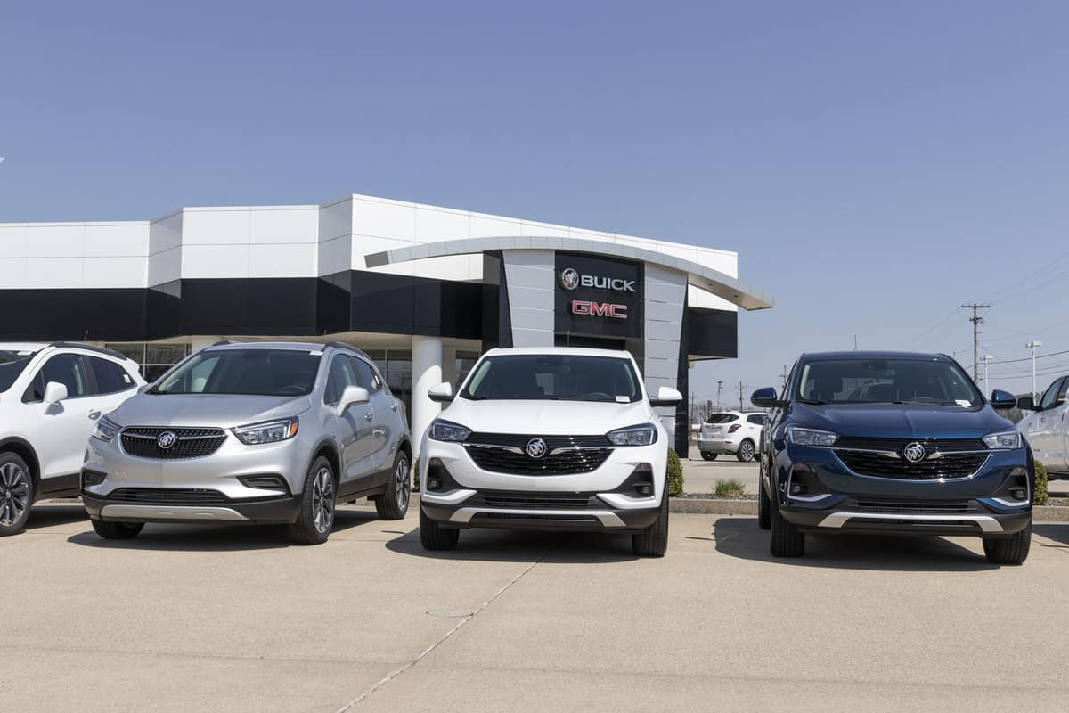 A line up of different colored Buick encores parked outside the GMC dealership