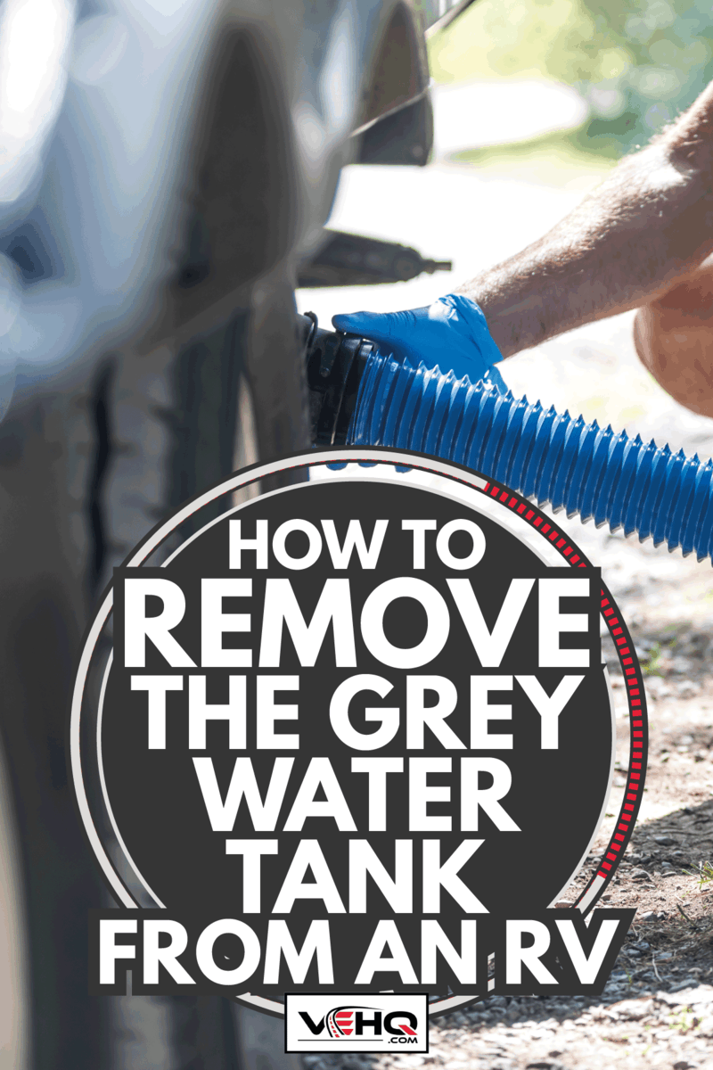 A man is emptying the RV sewer after camping. He is wearing gloves. How To Remove The Grey Water Tank From An RV