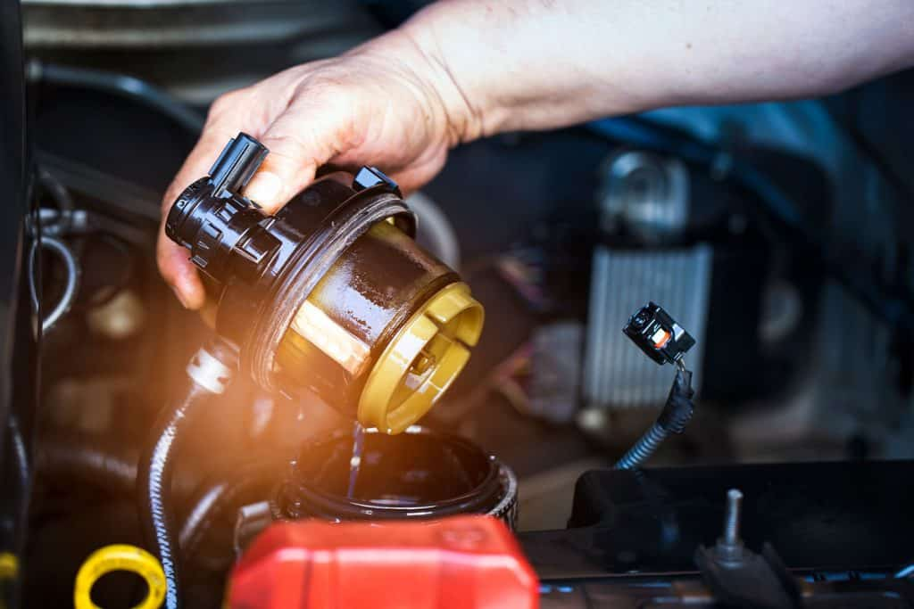 A mechanic checking the fuel filter of a car engine