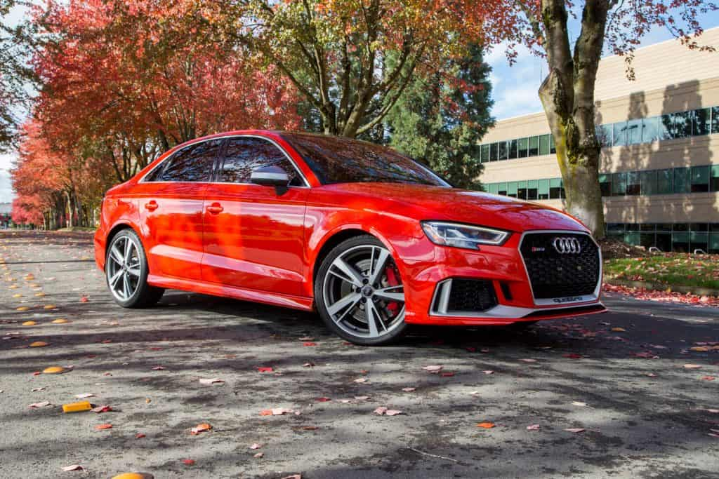 A red Audi RS3 luxury sports car is parked on a road covered with foliage leaves on a sunny fall day, Do Audi Cars Need Premium Gas? [Breakdown By Model]