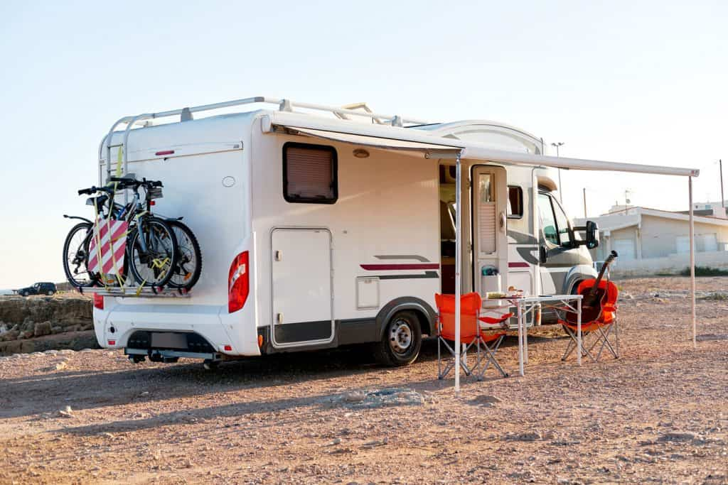 An RV parked near the beach with a tent setup outside its porch, RV Fireplace Not Working - What To Do