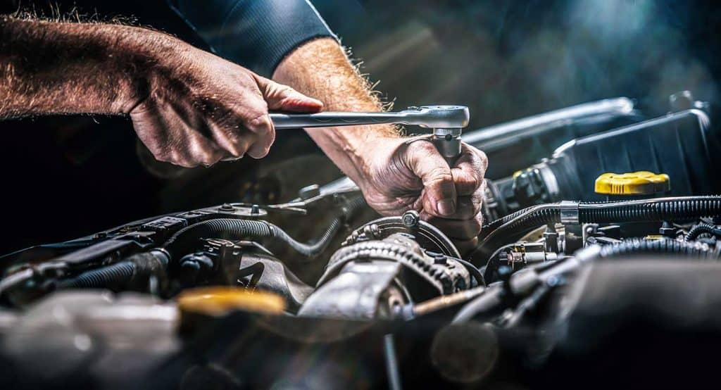 Auto mechanic working on car engine in mechanics garage