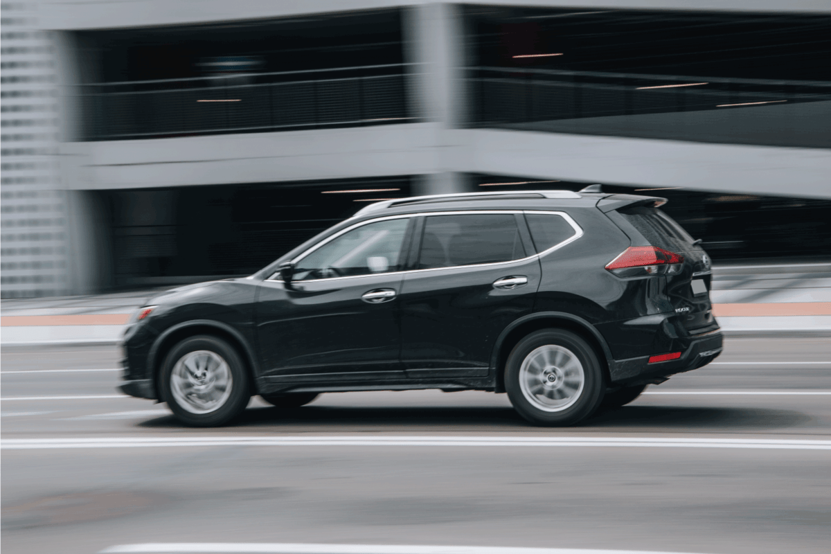 Black Nissan Rogue car moving on the street.