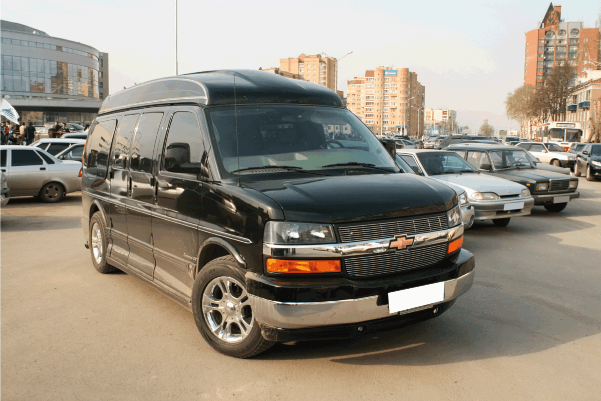 Black luxury van Chevrolet Express in the city street.