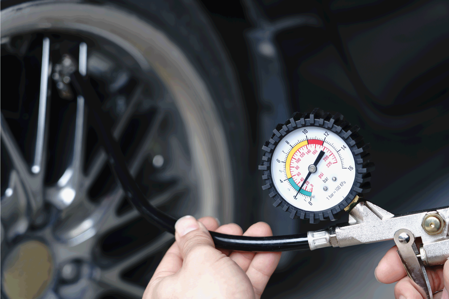 Close up mechanic inflating tire hand holding gauge pressure for checking and filling air in car tire.