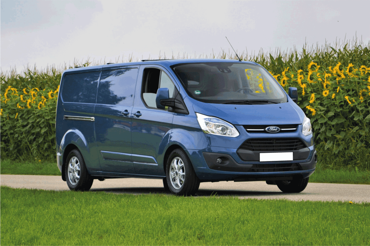 Ford Transit Custom stopped on the road. This model is one of the most popular delivery vans in Europe.