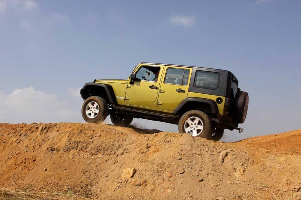 Green Jeep Wrangler Unlimited scaling tilt bridge obstacle