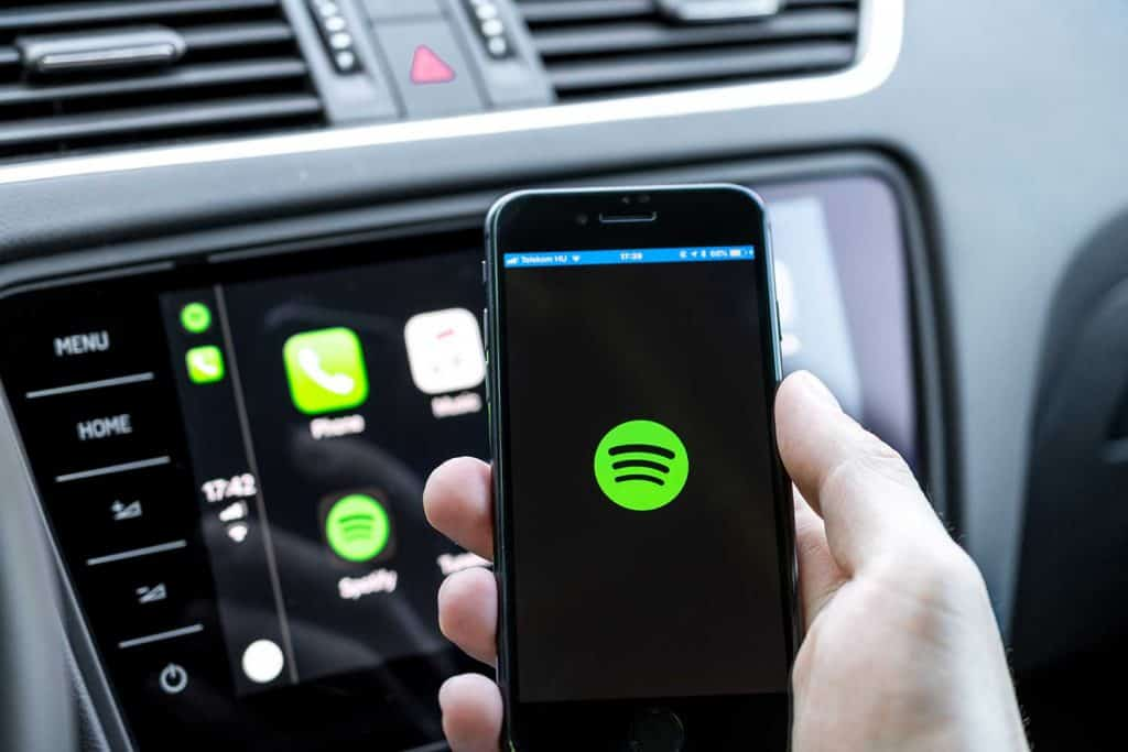 Hand holding a smartphone connecting to the car's computer running a music streaming service