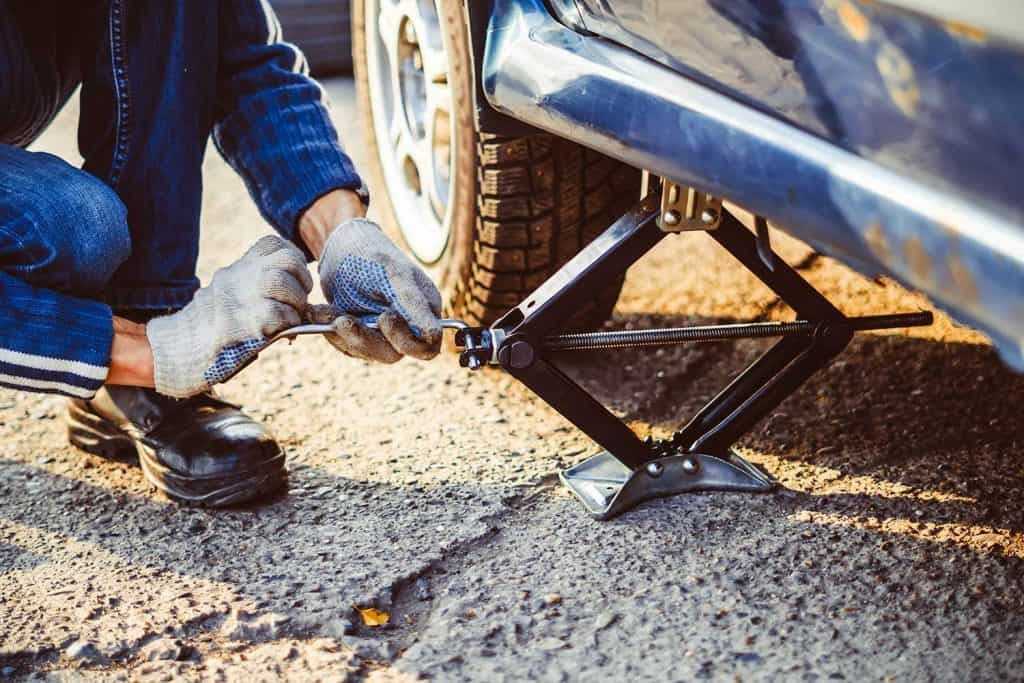 Jacking up a car to change a tyre with the hydraulic jack