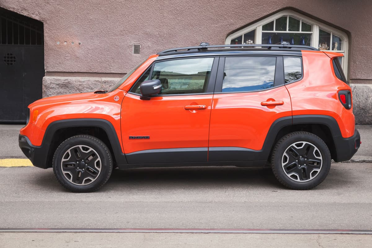 Light red colored jeep renegade on the side of a building