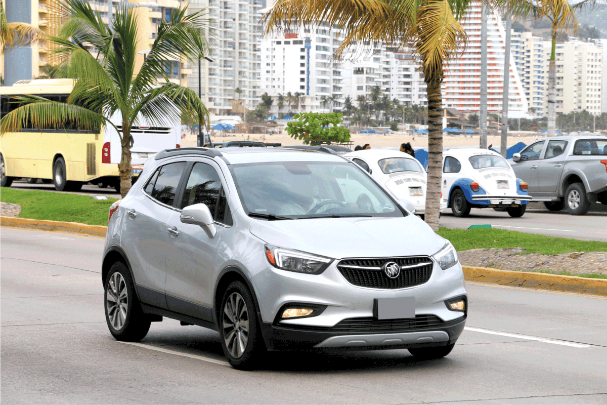 Motor car Buick Encore in the city street with palm trees