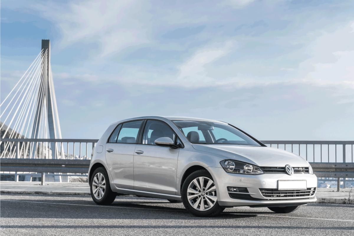 New Volkswagen Golf VII parked in front of a bridge