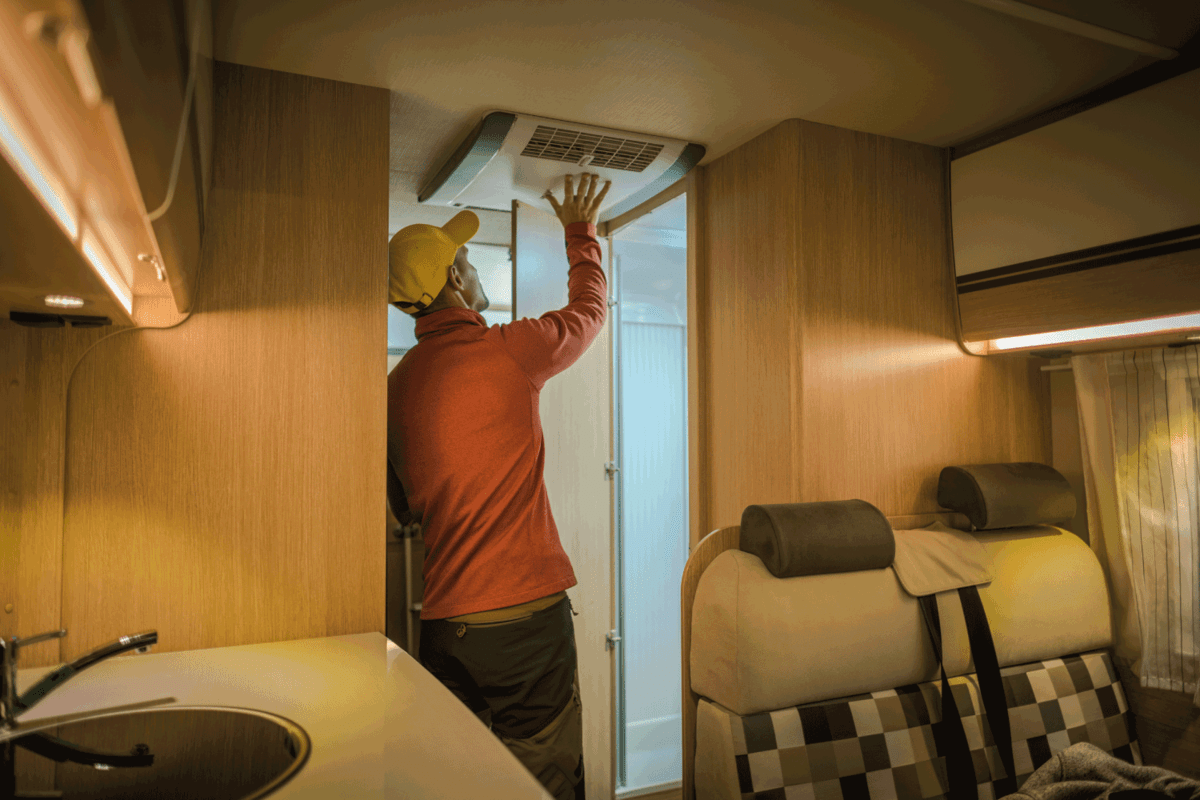 RV Air Conditioner Check. Man Checking Camping Motorhome Appliances Before Summer Travel Season.