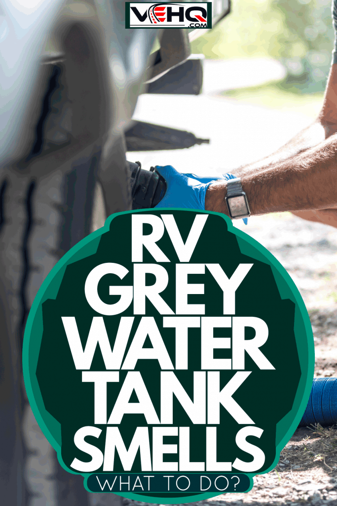 A man attaching a blue waste hose to the grey water tank, RV Grey Water Tank Smells - What to Do?
